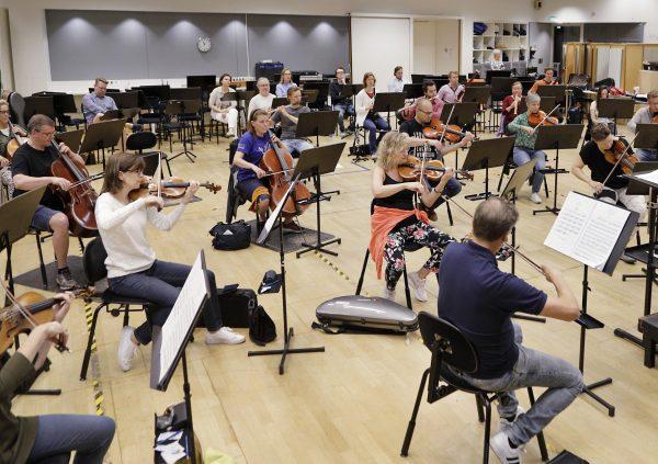 Orkesteri soittaa turvavälit huomioon ottaen harjoitussalissa
